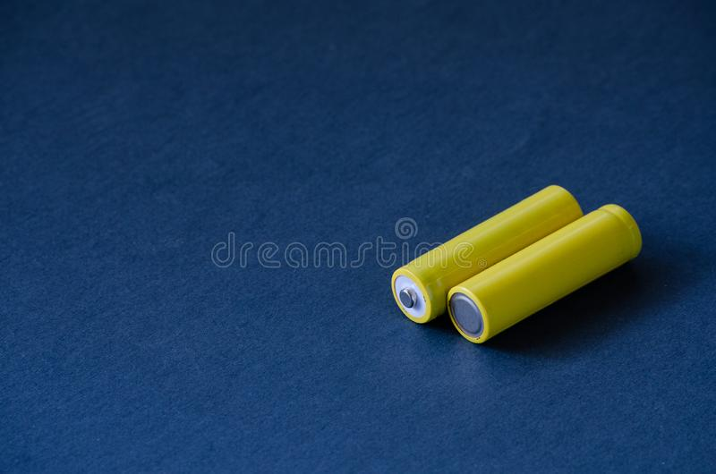 Rechargeable yellow R6 AA batteries on dark background royalty free stock image