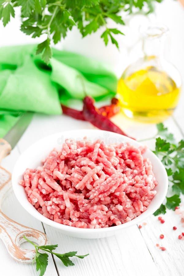 Recheio de carne Carne de carne de porco à terra crua na bacia na mesa de cozinha branca Carne triturada fresca fotografia de stock