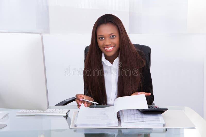 Rechensteuer der überzeugten Geschäftsfrau am Schreibtisch stockbild