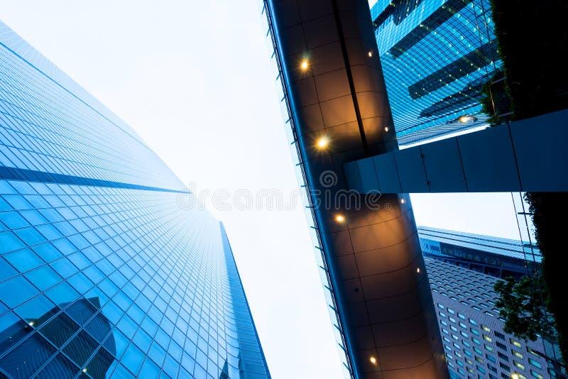 recherchant la vue dans le secteur financier, les silhouettes des gratte-ciel que la ville reflètent le ciel bleu dramatique, le  images libres de droits
