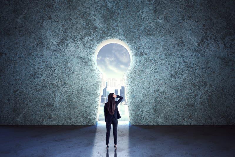 Rechercher une solution avec une femme d'affaires qui reste devant le trou de serrure dans un grand mur en béton image stock