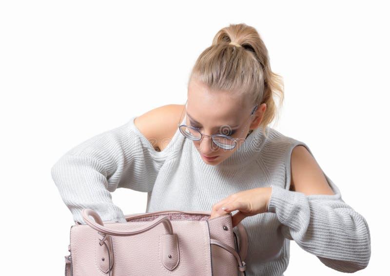 Recherches de jeune femme dans un sac à main photo stock