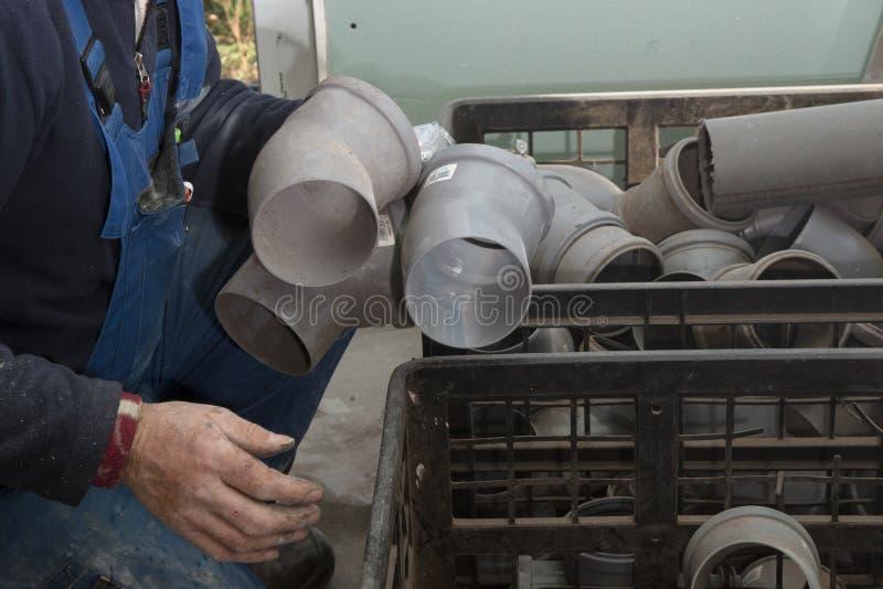 Recherches sanitaires d'installateur dans une grande boîte pour une courbure appropriée de connexion pour le tuyau des eaux usées photographie stock