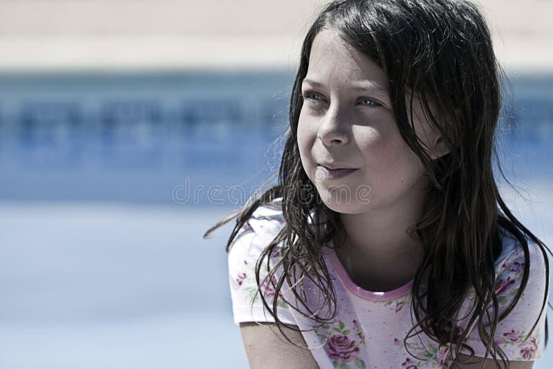 Recht aber unordentliches Brown-behaartes Mädchen durch das Pool stockfotos