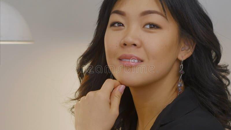 Recht asiatische Frau, die durch das Fenster mit einem Lächeln schaut stockfotos