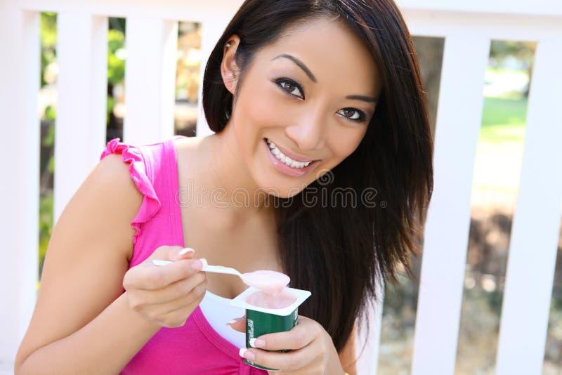 Recht asiatische Frau, die Joghurt isst stockbild