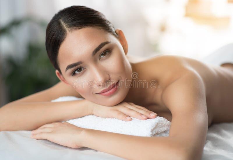 Recht asiatische Frau, die am Schönheitssalon liegt stockfoto