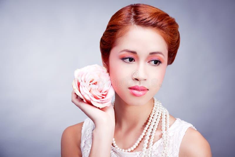 Recht asiatische Frau mit Blume und Perlen lizenzfreie stockfotografie