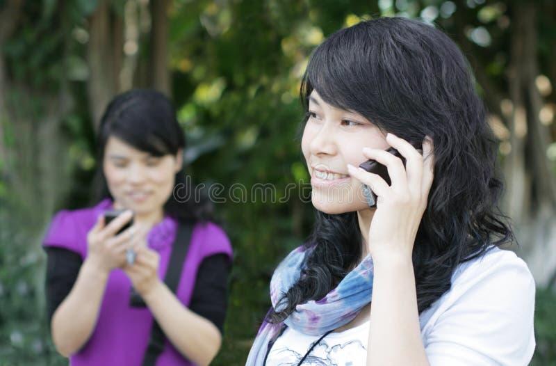 Recht asiatische Mädchen, die einen Handy verwenden lizenzfreies stockfoto