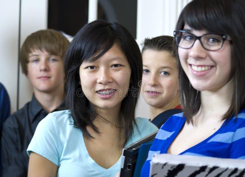 Recht asiatisches Mädchen mit Mitschülern stockfotografie