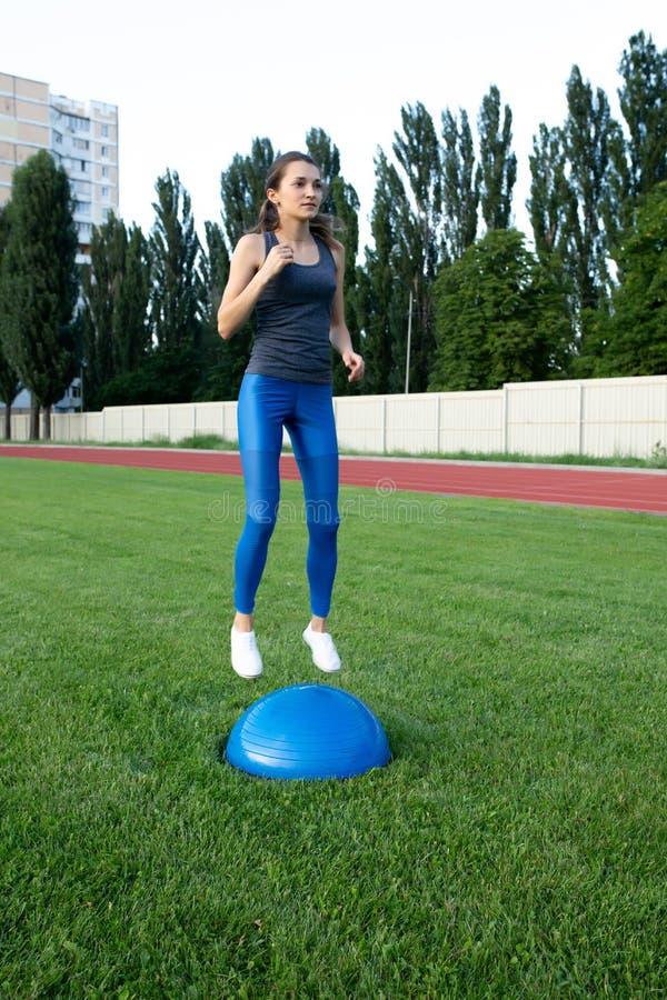 Recht athletisches Frauentraining mit bosu Ball am Stadion lizenzfreie stockfotografie