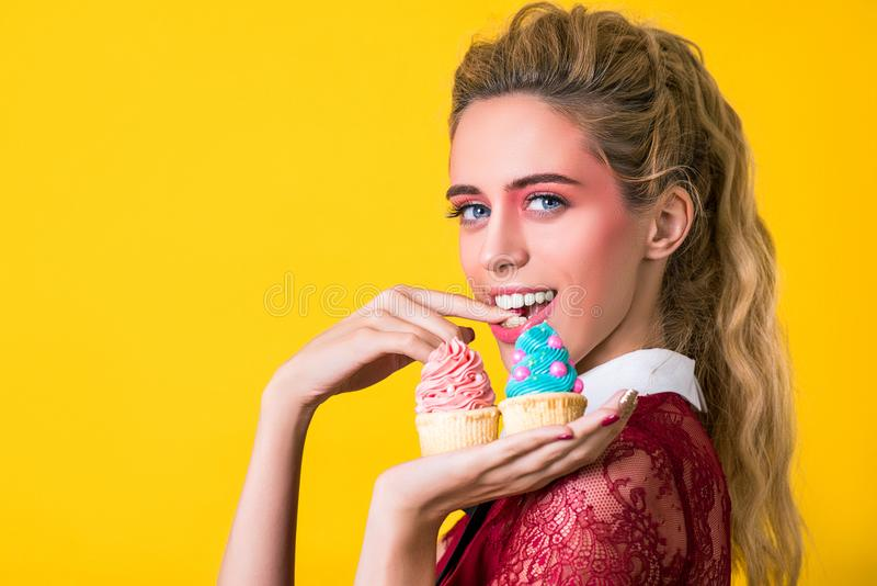 Recht attraktive lächelnde Frau bietet zwei geschmackvollen kleinen Kuchen an lizenzfreie stockfotografie