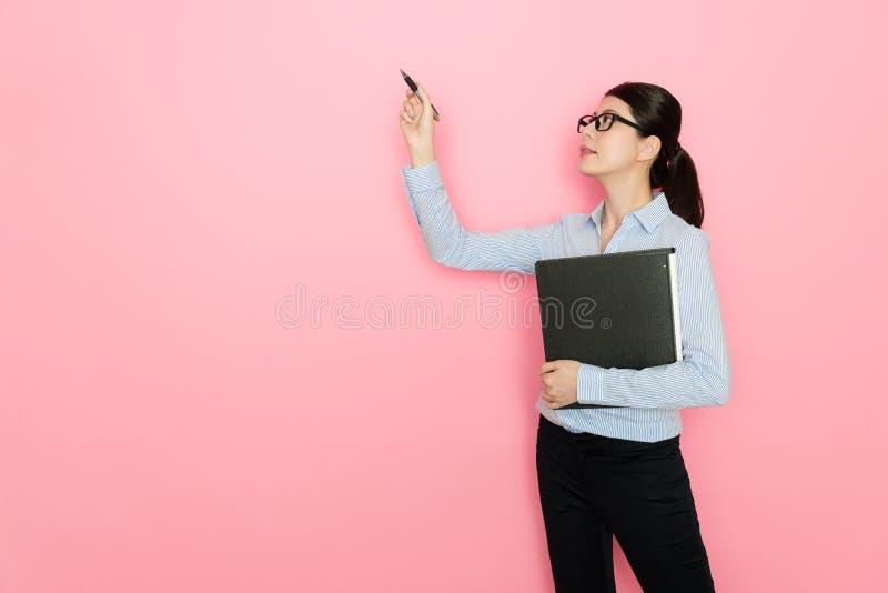 Recht attraktiver FrauenBüroangestellter, der Stift verwendet stockfotos