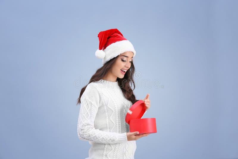 Recht aufgeregte Dame in der Weihnachtshut-Öffnungsgeschenkbox lizenzfreie stockfotos