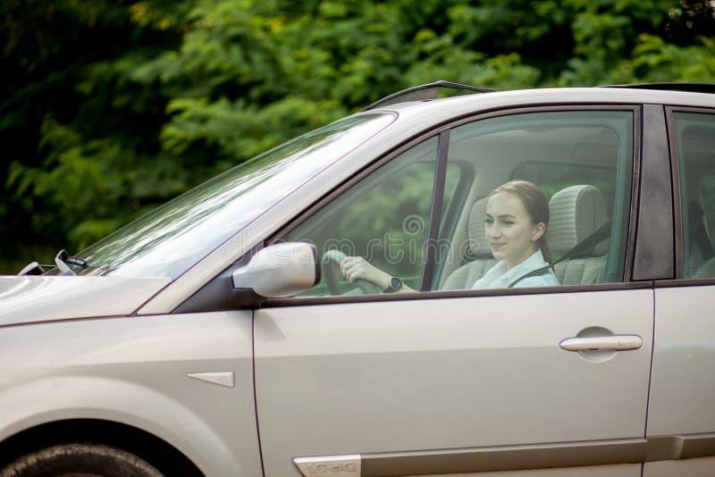 Recht Autofahren der jungen Frau - Einladung zu reisen Automiete oder Ferien stockbild