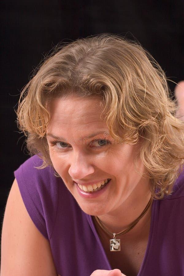 Recht blonde Frau auf schwarzem Hintergrund stockbild