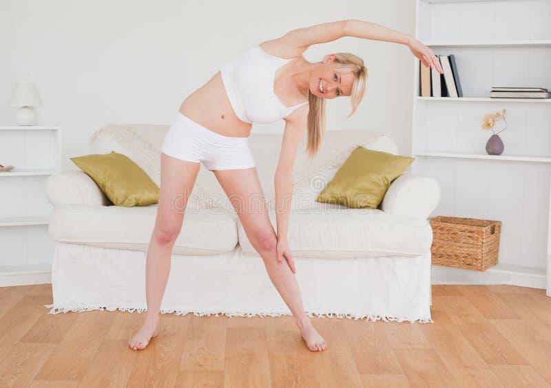 Recht blonde Frau, die in das Wohnzimmer ausdehnt stockbilder