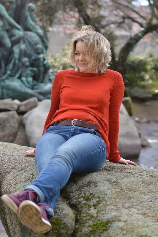 Recht blonde Frau, die in einem Park auf einem Felsenlächeln sitzt lizenzfreies stockbild
