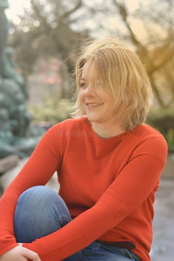 Recht blonde Frau, die in einem Park mit Hintergrundbeleuchtung sitzt lizenzfreies stockbild