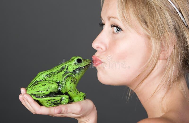 Recht blondes Mädchen, das einen Frosch küßt stockfotos
