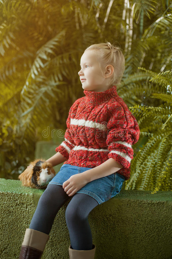 Recht blondes Mädchen, das im Park mit ihrem Haustier aufwirft stockbilder