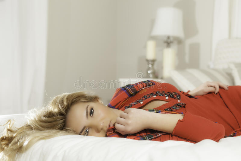 Recht blondes Mädchen im roten Legen auf Bett-Lampen-Hintergrund stockfotografie