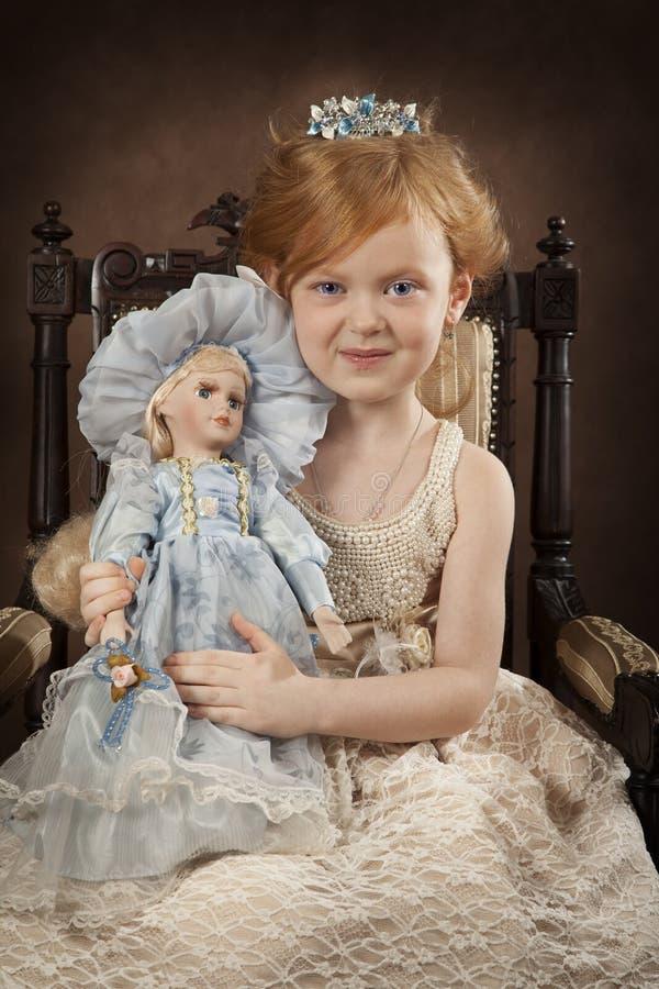 Recht blondes Mädchen mit einer Puppe lizenzfreies stockfoto