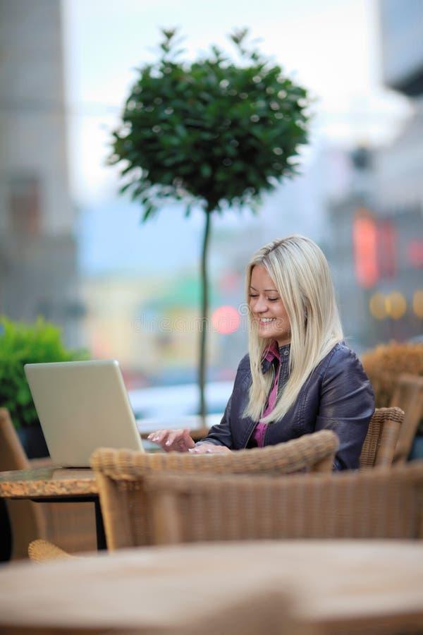 Recht Blondine mit Laptop im Straßenkaffee lizenzfreie stockfotos