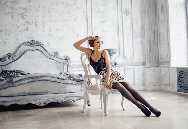 Recht dünne Brunettefrau, die im Luxusraum stillsteht stockfotografie