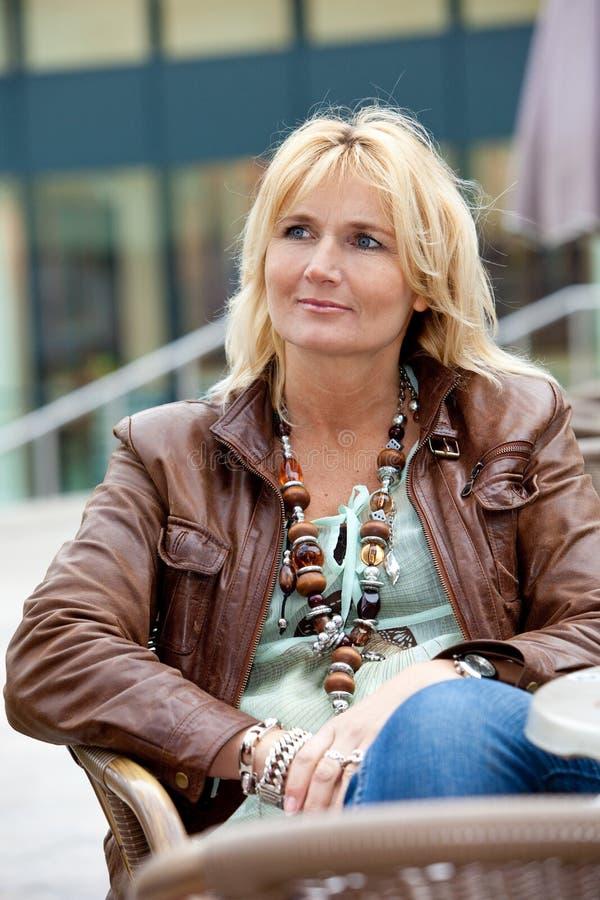 Recht fällige Frau auf einer Terrasse stockbilder