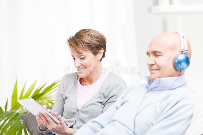 Recht Frau von mittlerem Alter, die eine Tablette verwendet stockfoto