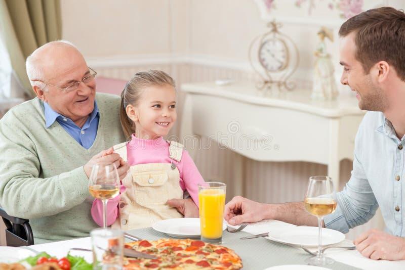 Recht freundliche Familie isst mit Freude zu Abend lizenzfreies stockbild