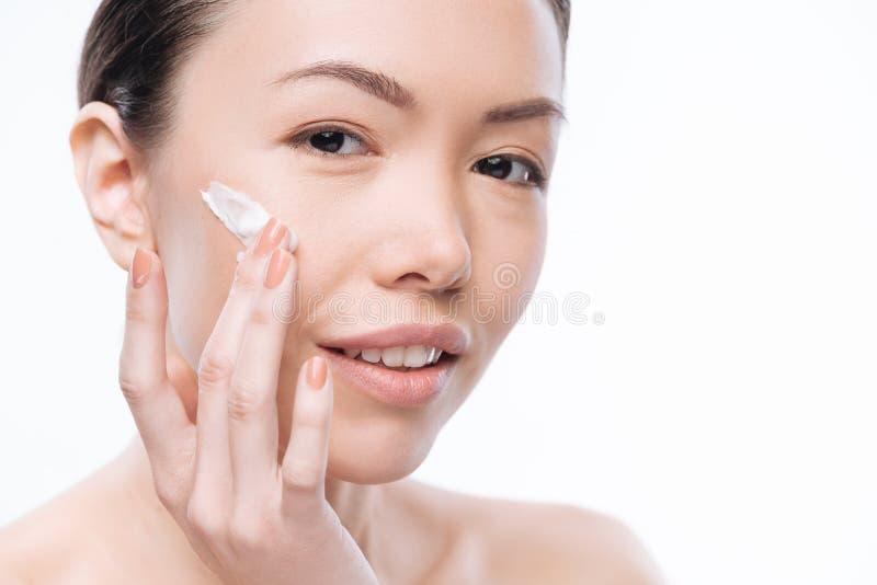 Recht frohe Frau, die Gesichtscreme verwendet lizenzfreie stockfotografie