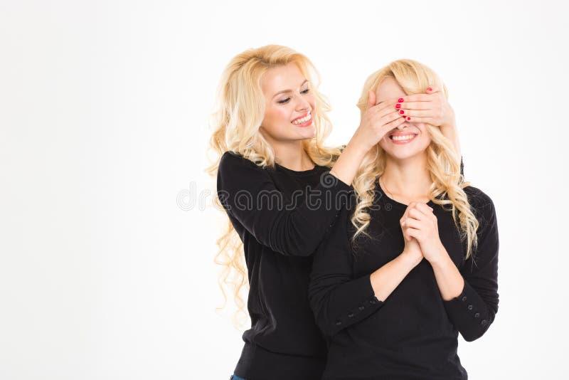 Recht froher blonder Schwesterzwilling bedeckte die Augen zu anderen lokalisiert lizenzfreie stockfotografie