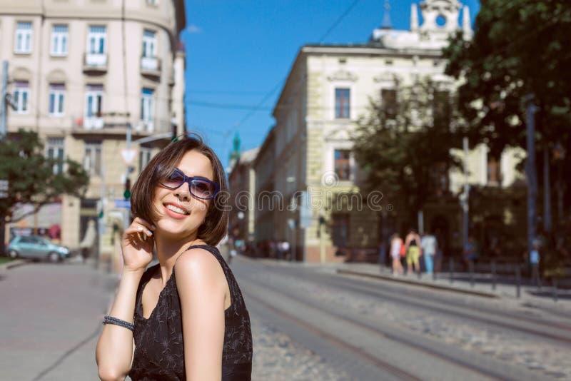Recht gebräunte lächelnde tragende Gläser der Frau und stilvolles Kleid, p lizenzfreies stockfoto