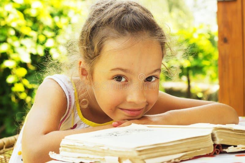 Recht gelocktes Schulmädchen, das draußen ein altes Buch liest lizenzfreie stockfotos