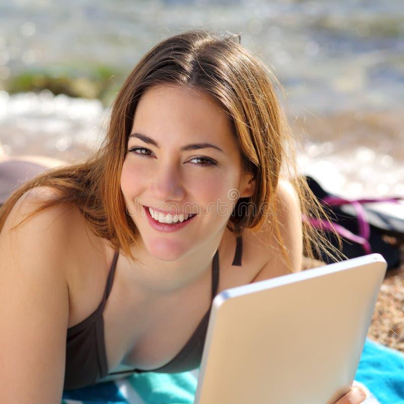 Recht glückliche Frau, die eine Tablette auf dem Strand verwendet lizenzfreie stockbilder