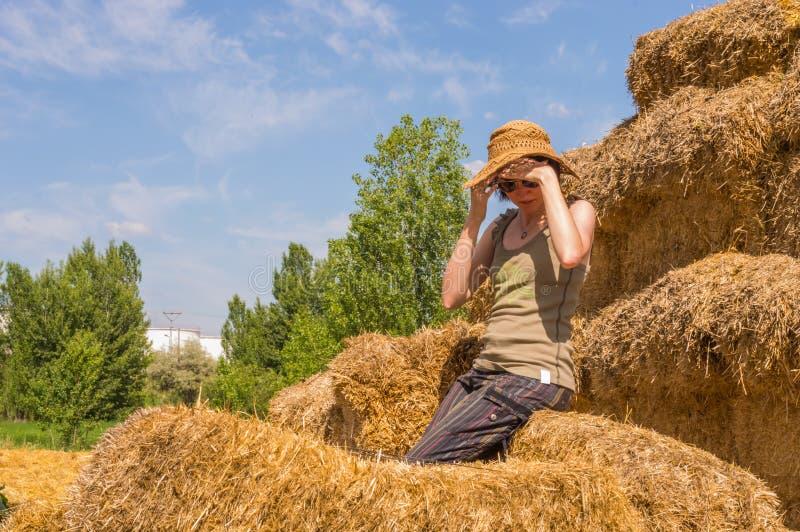 Recht glückliche Frau mit dem Hut, der auf Stroh sitzt, emballiert die Abdeckung ihrer Augen mit ihren Händen lizenzfreie stockfotos