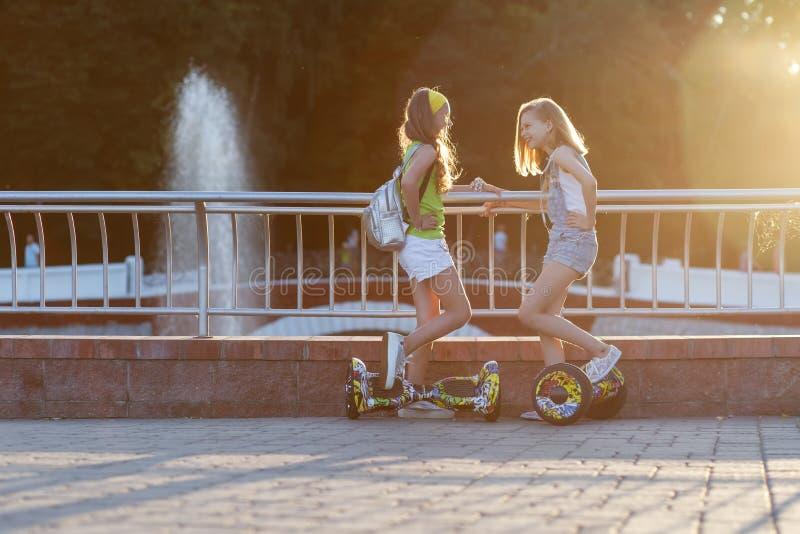recht glückliches Reiten des Mädchens zwei auf Schwebeflugbrett oder gyroscooter draußen bei Sonnenuntergang im Sommer Berufslebe lizenzfreie stockfotos