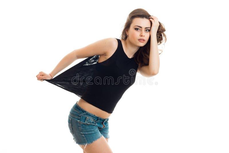 Recht interessanter junger Brunette, der im Studio in einem T-Shirt und in den kurzen Hosen aufwirft lizenzfreie stockbilder