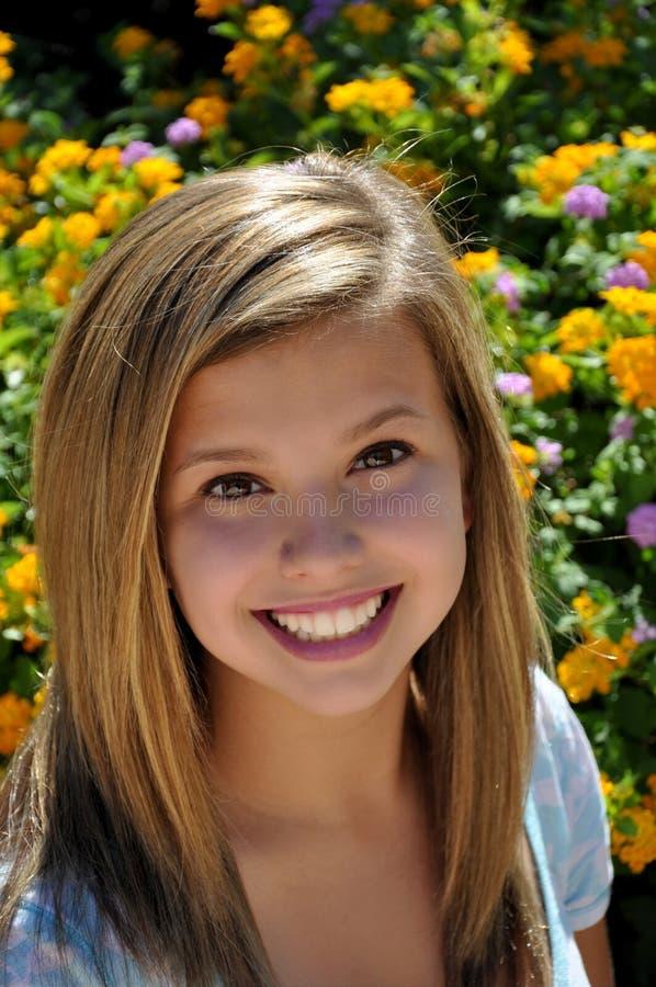 Recht jugendlich großes Lächeln nahe bei Blumengarten lizenzfreie stockbilder