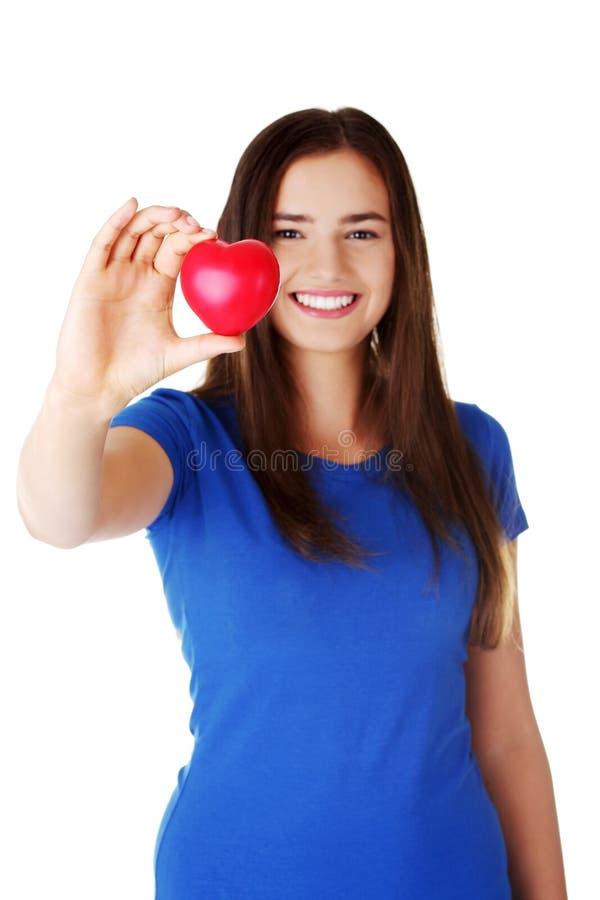 Recht jugendlich Mädchen, das rotes Herz zeigt. lizenzfreie stockbilder