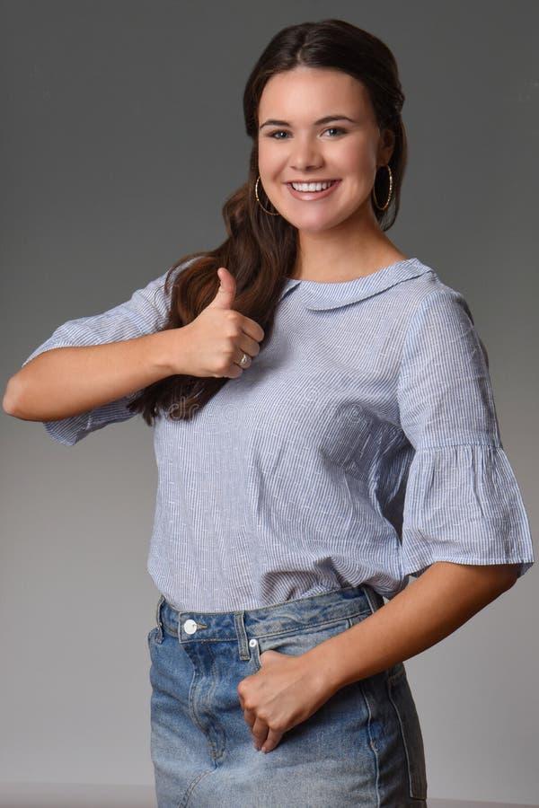Recht jugendlich Mädchen mit schönem Lächeln gibt Daumen auf lizenzfreies stockfoto