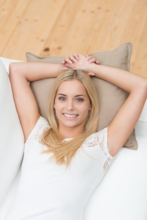 Recht junge blonde Frau, die auf einem Sofa liegt stockbild