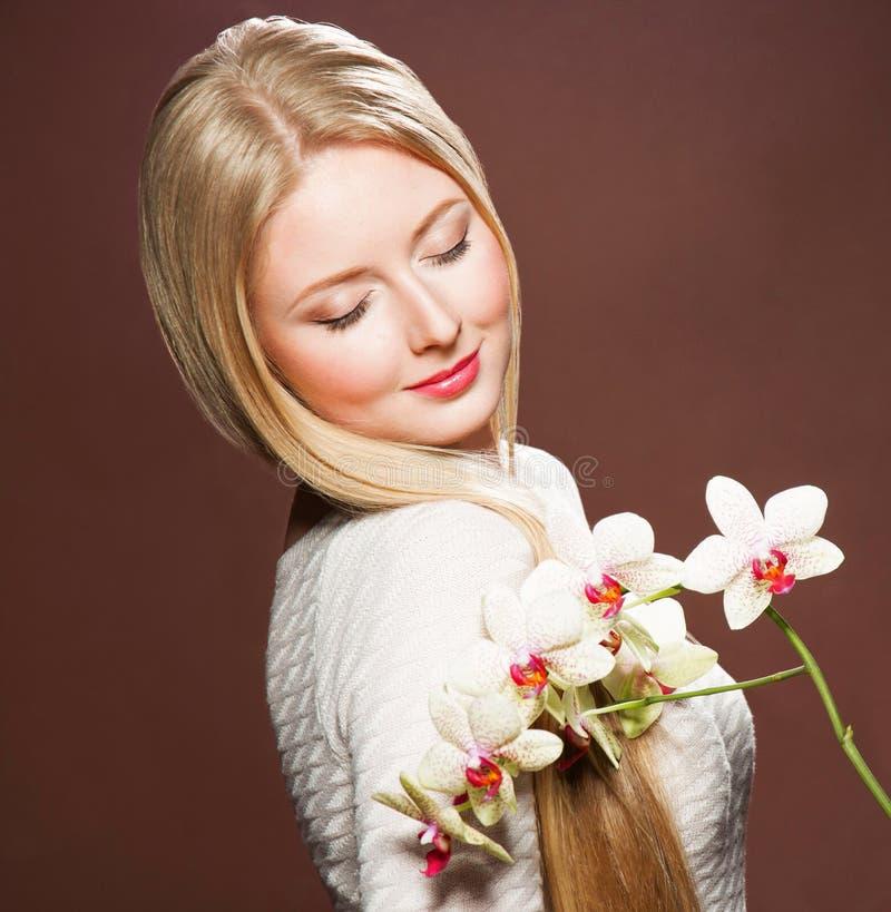 Recht junge Blondine mit schöner Haar- und Blumenorchidee lizenzfreies stockfoto