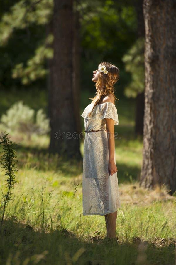Recht junge Boho-Frau, die im Wald steht stockfotografie