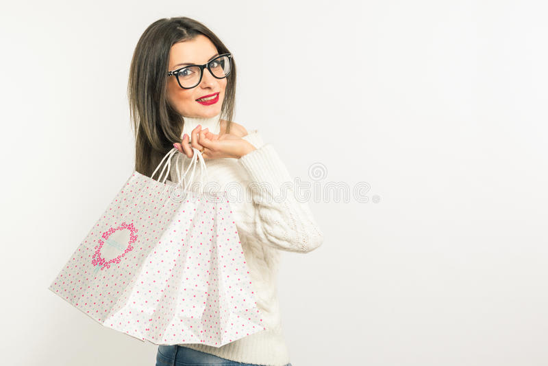 Recht junge Brunettefrau in den Gläsern und eine weiße Strickjacke, die Einkaufstaschen steht und hält Auf einem weißen Hintergru stockbilder