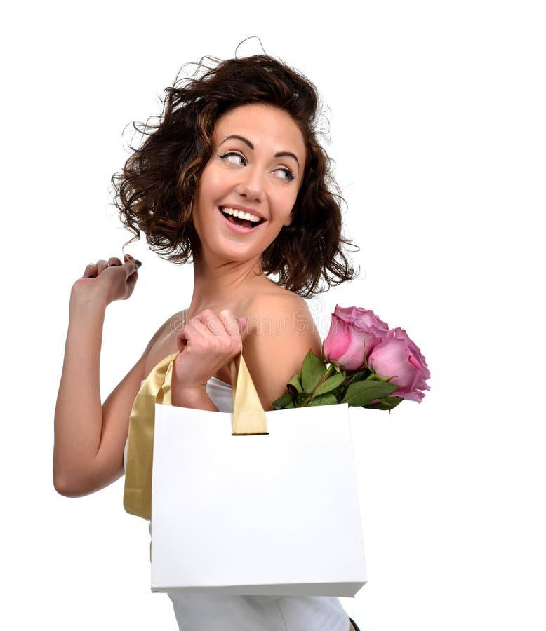 Recht junge Brunettefrau mit Einkaufstaschegoldstreifen und purpurroten Rosen blüht lizenzfreie stockbilder