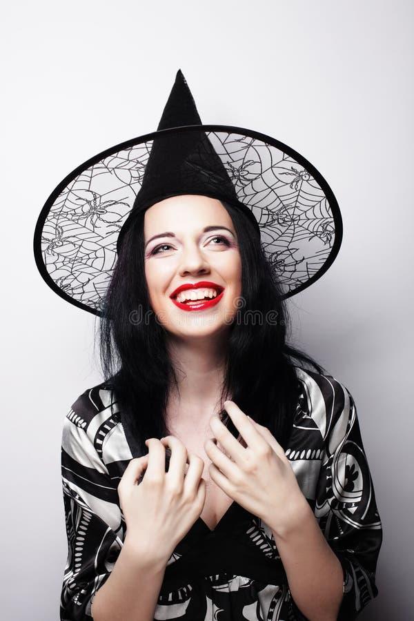 Recht junge Brunettehexe mit schwarzem Hut stockfotografie