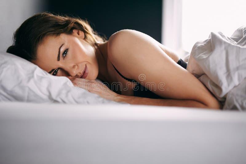 Recht junge Dame, die auf Bett liegt stockfotografie
